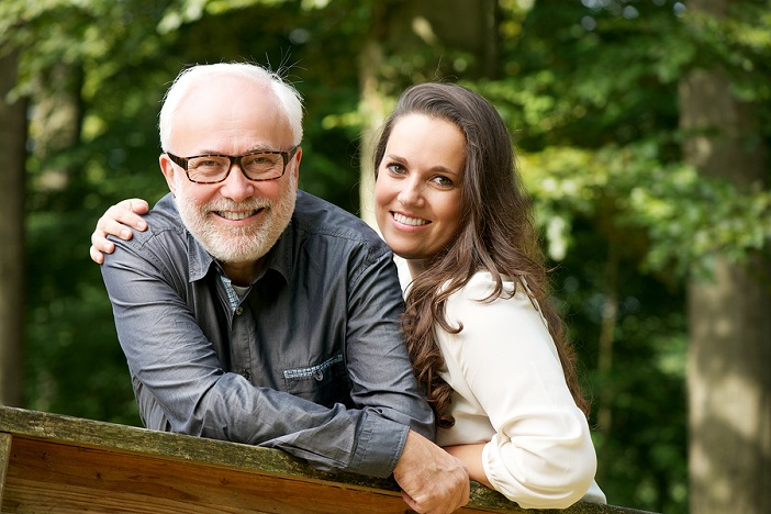 Happy older Man Smiling With Young Woman